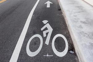 Signo de bicicleta en carril bici en carretera asfaltada