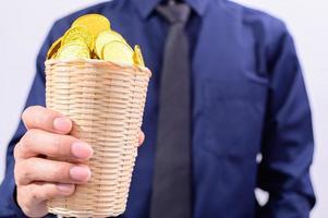 mano sosteniendo una canasta llena de monedas