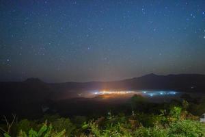Starry night sky over a city photo