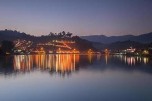 Village lights reflected in water at night