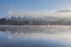niebla y reflejo de la aldea en el agua foto