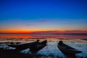 Colorful sunset with longboats in the water photo