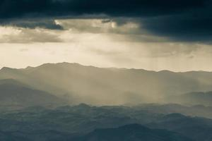Misty sunrise over mountains photo