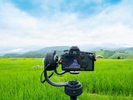 cámara de video y un campo verde. foto