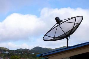 Satellite dish on a roof during the day photo