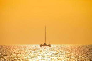 Boat on the water with an orange sunset