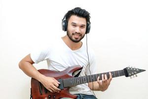 Young Asian man playing guitar photo