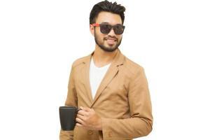 Hombre asiático con bigote sonriendo sobre fondo blanco sosteniendo una taza de café