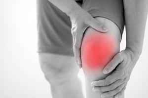 lesión de rodilla aislada en rojo foto