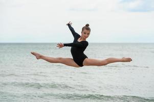 joven gimnasta saltando cerca del agua
