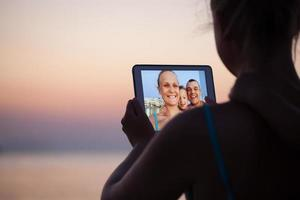 Family virtually connecting on a beach