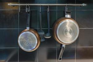 Sartén de hierro y utensilios colgados en la pared. foto