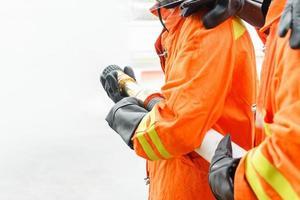 Bomberos usando extintor y agua de manguera.