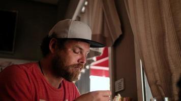 cara comendo um sanduíche em um café video