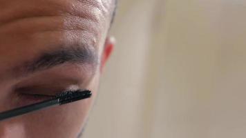 homem pinta cílios com rímel