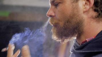 homem barbudo fuma um cigarro