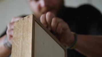 carpintero cepilla una caja de madera