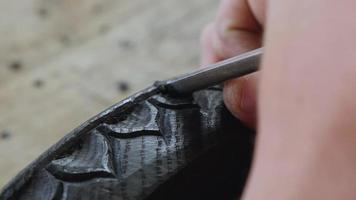 Woodcarver sculpte un motif sur un chêne des marais