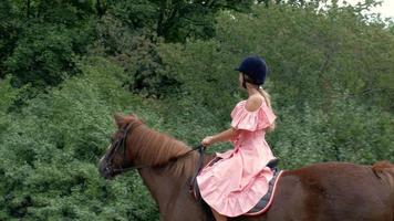 garota monta um cavalo marrom