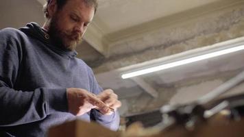 El hombre muele un trozo de madera con papel de lija