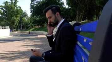 homem usando um telefone celular em um banco