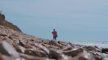 homem caminha ao longo do mar