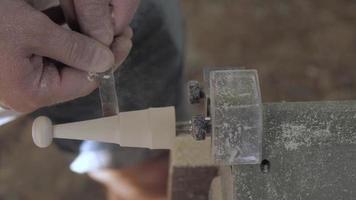 Man Shaping Piece of Wood on Wood Turning Lathe
