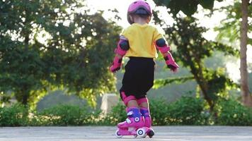 Little Girl Learning to Roller Skate in A Summer Park