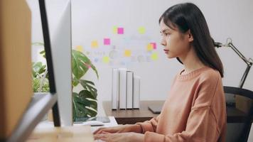 Mujer asiática concentrada trabajando en una computadora