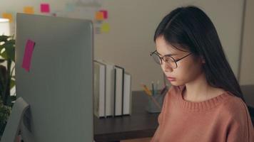 mujer con dolor de cabeza trabajando en una computadora