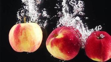 maçãs maduras caindo na água