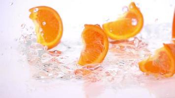 várias fatias de laranja estão caindo sobre a mesa