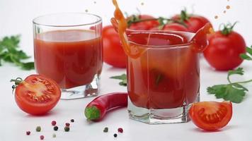 tomate maduro cai em um copo de suco de tomate