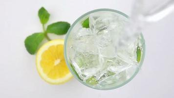vertiendo soda en un vaso con los cubitos de hielo