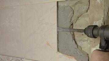 martelo de demolição quebrando a parede de azulejos