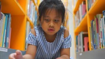 niña leyendo entre muchos libros en la biblioteca video
