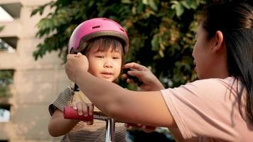 Young mother helping her daughter with pink helmet .