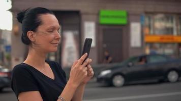 morena usando el móvil en la ciudad