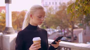 portret blonde maakt gebruik van telefoon in de stad