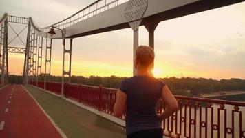 Unrecognizable jogger female runs on the bridge