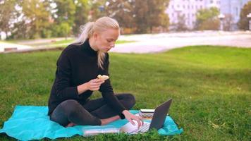 menina caucasiana comendo sanduíche enquanto trabalha ao ar livre