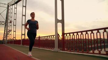 Jogger female runs on the bridge