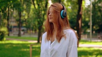 Woman using headphones and listening to music outdoors