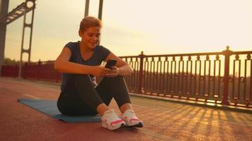 Mädchen mit Telefon nach dem Training in der Brücke