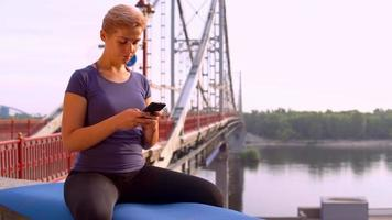 Sportlerin nutzt App auf dem Handy