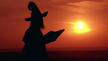 Silhouette girl in fancy dress and witch hat casts a spell sunrise view