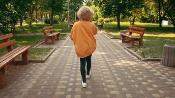Mujer con cabello rubio mediante paseos móviles al aire libre
