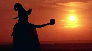 Silhouette Girl in fancy dress and sorceress hat sunrise view