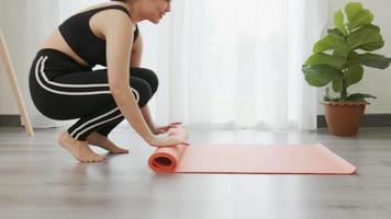 mulher rola o tapete de ioga laranja video