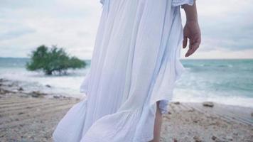primo piano delle gambe di una donna triste su una spiaggia